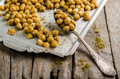 Roasted spicy chickpeas with zaatar or zatar on vintage metall try and wooden background. Top view Stock Photos