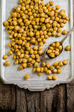 Roasted spicy chickpeas with zaatar or zatar on vintage metall try and wooden background. Top view Royalty Free Stock Photography