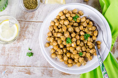 Roasted spicy chickpeas with zaatar or zatar on vintage metall try and wooden background. Top view Royalty Free Stock Photo