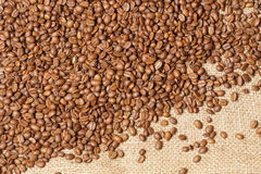 Roasted spilled coffee beans on sackcloth background Royalty Free Stock Photography