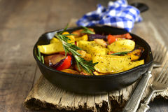 Roasted spring vegetables with rosemary and garlic. Roasted spring vegetables with rosemary and garlic in a skillet pan on a wooden background stock images