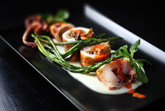 Roasted squid on black dish. Royalty Free Stock Photography