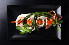Roasted squid on black dish. Stock Photos