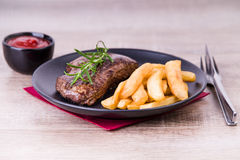 Roasted steak with french fries and onions royalty free stock photography