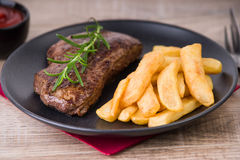 Roasted steak with french fries and onions royalty free stock photo