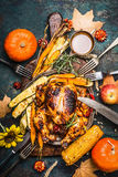 Roasted stuffed whole turkey or chicken with organic harvest vegetables and pumpkin for Thanksgiving dinner served on rustic cutt Stock Image