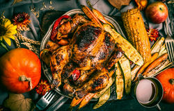 Roasted stuffed whole turkey or chicken with organic harvest vegetables and pumpkin for Thanksgiving dinner served on rustic tabl Stock Image