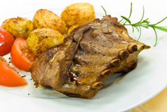 A roasted suckling pig with potatoes and salad Stock Images