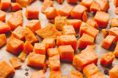 Roasted sweet potato cubes on a baking paper. Roasted sweet potato cut in small cubes on a baking paper royalty free stock image