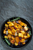 Roasted Sweet Potato with Red Onion and Rosemary. Black dish, overhead view, over dark slate Royalty Free Stock Image