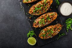 Roasted sweet potato stuffed with chickpeas and quinoa, served w. Ith garlic yogurt sauce. Top view. black background royalty free stock photography