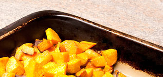 Roasted Sweet Potatoes. In a stoneware pan, horizontal stock photography