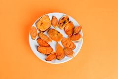 Roasted sweet potatoes on the grill pan on the plate close-up. Shot from above. royalty free stock photos