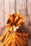 Roasted sweet potatoes with herbs in a paper cone close-up. vert Stock Photo