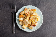 Roasted Sweet Potatoes and Parsnips. On a blue china plate on a dark concrete background top view royalty free stock photo
