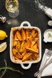 Roasted sweet potatoes in white ceramic dish. Wine, dip, lemon, salt and rosemary around Royalty Free Stock Photography
