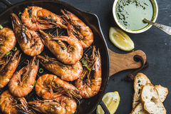 Roasted tiger prawns in iron grilling pan with fresh leek, lemon slices, bread and pesto sauce over black background Stock Images