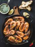 Roasted tiger prawns in iron grilling pan on wooden board with fresh leek, lemon slices, pepper, bread and pesto sauce Stock Photo