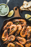 Roasted tiger prawns in iron pan on wooden board with fresh leek, lemon slices, bread and pesto sauce over black Stock Photo