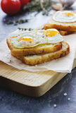 Roasted toasts with quail eggs. Seasoned with sea salt and a thyme on a kitchen board Stock Photo