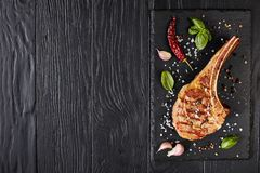 Roasted tomahawk steak on a board. Roasted tomahawk steak or cowboy beef steak on a black slate board with garlic, fresh basil, view from above, flat lay stock photos