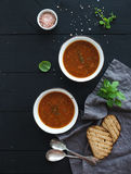 Roasted tomato soup with fresh basil, spices and bread in rustic metal bowls over black background Stock Photo