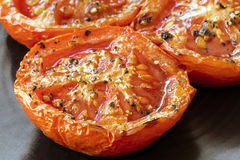 Roasted Tomatoes on Black Plate Side View Closeup Royalty Free Stock Photography