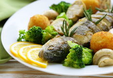 Roasted trout fish with vegetables and lemon Stock Photos