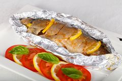 Roasted trout. With tomato and lemon stock images