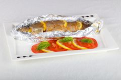 Roasted trout. With tomato and lemon stock image