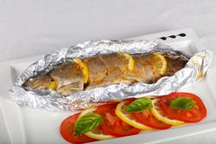Roasted trout. With tomato and lemon stock photo