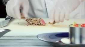 Roasted tuna with sesame seeds. Hands of chef, seafood stock video