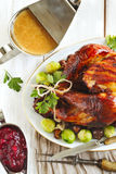 Roasted turkey with bacon and garnished with chestnuts and brussels sprouts. Royalty Free Stock Photography