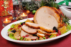 Roasted turkey breast. Sliced baked turkey ham with fruit garnish on the Christmas table Royalty Free Stock Image