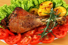 Roasted turkey drumstick with vegetables. Closeup Royalty Free Stock Photo