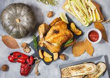 Roasted turkey and grilled zucchini, eggplant and pepper on a rustic concrete table decorated with walnut and autumn leaf. Flat la. Y. Top view stock image