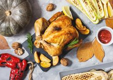 Roasted turkey and grilled zucchini, eggplant and pepper on a rustic concrete table decorated with walnut and autumn leaf. Flat la. Y. Top view royalty free stock photography