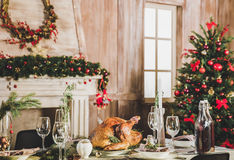 Roasted turkey on holiday table. Delicious roasted turkey on served holiday table decorated for Christmas Royalty Free Stock Images