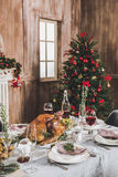 Roasted turkey on holiday table. Delicious roasted turkey on served holiday table decorated for Christmas Royalty Free Stock Photography