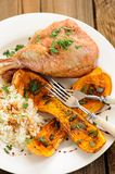 Roasted turkey leg with butternut squash, pumpkin seeds and rice Stock Photos