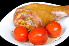Roasted turkey leg with tomatoes Stock Image