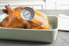 Roasted turkey with meat thermometer in baking dish. On table stock photos