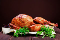 Roasted Turkey. Thanksgiving table served with turkey, decorated with greens and basil on dark wooden background. Homemade roasted Stock Photos