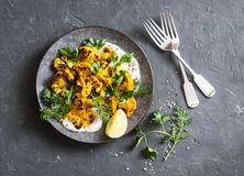 Roasted turmeric cauliflower with greek yogurt dressing. Delicious healthy snack on a dark background Royalty Free Stock Images