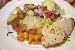 Roasted veal meat with potatoes, jerusalem artichokes. And salad Stock Photo