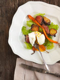 Roasted-vegetable salad with poached eggs stock photos