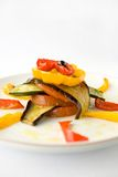 Roasted vegetables. Assorted roasted vegetables arranged on a white plate, zucchini, red bell peppers, yellow bell peppers, tomatoes, drizzled with olive oil Royalty Free Stock Photography