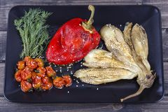 Roasted vegetables - eggplant and red pepper with tomato salsa in black plate. Close up royalty free stock image