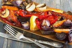 Roasted vegetables, fork and knife. Stock Images
