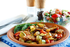 Roasted vegetables and fresh salad. Roasted vegetables on a rustic plate. Salad with fresh vegetables and spices in the background. Isolated on white Royalty Free Stock Images